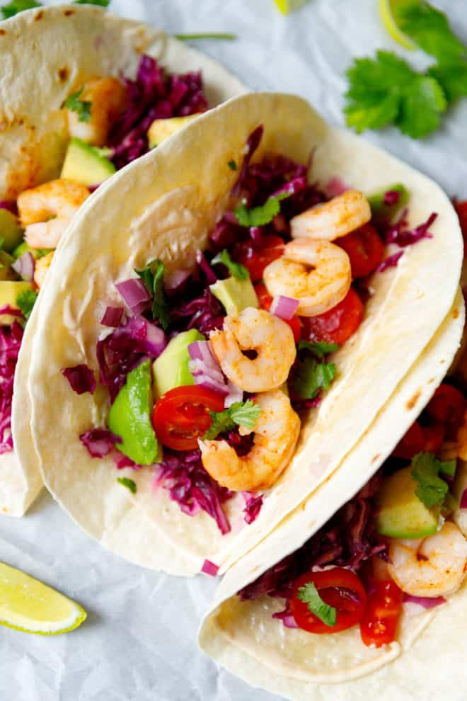 Shrimp tacos next to each other with red cabbage, tomatoes, lime wedges