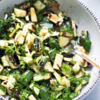 A bowl full of mouthwatering chopped grilled zucchini pieces, topped with fresh chopped parsley, dill, garlic, balsamic, apple cider vinegar and olive oil. Gread side dish for grilled meat, chicken or fish.