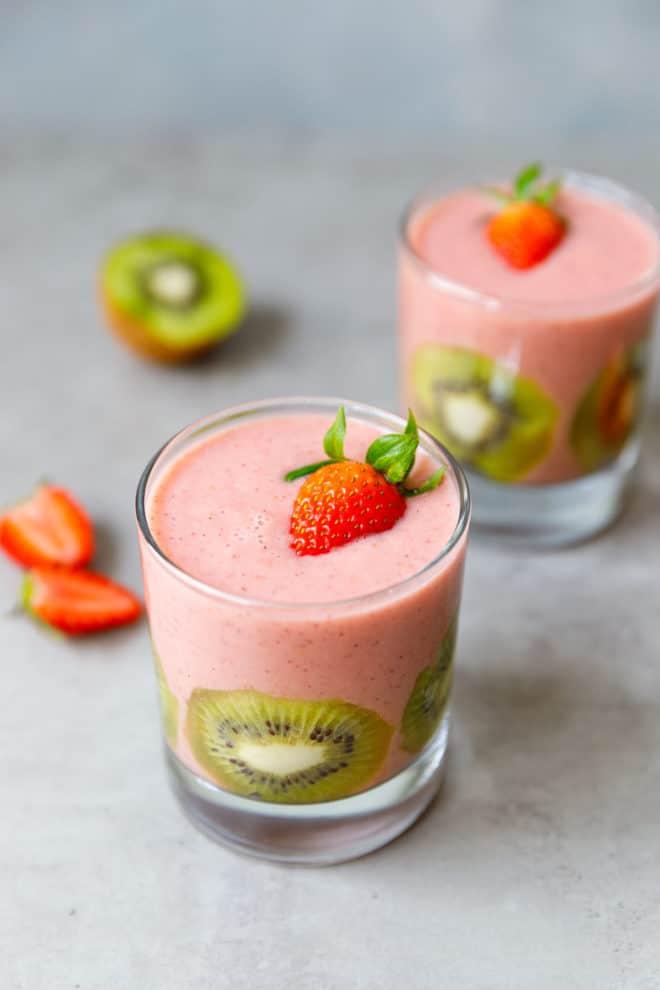 A clear glass with strawberry kiwi banana smoothie