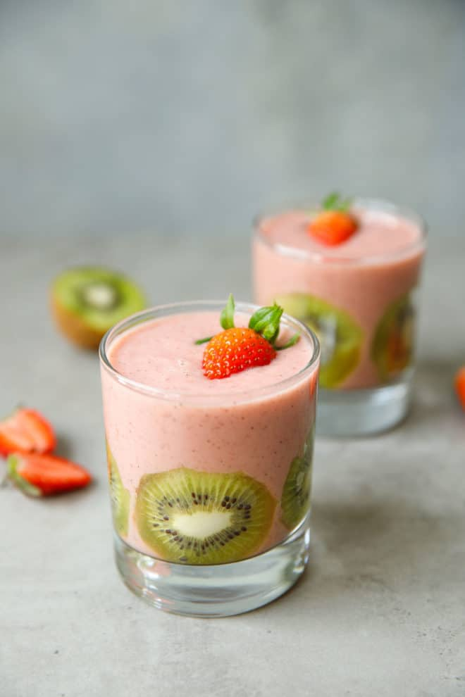 Two clear cups with strawberry kiwi smoothie