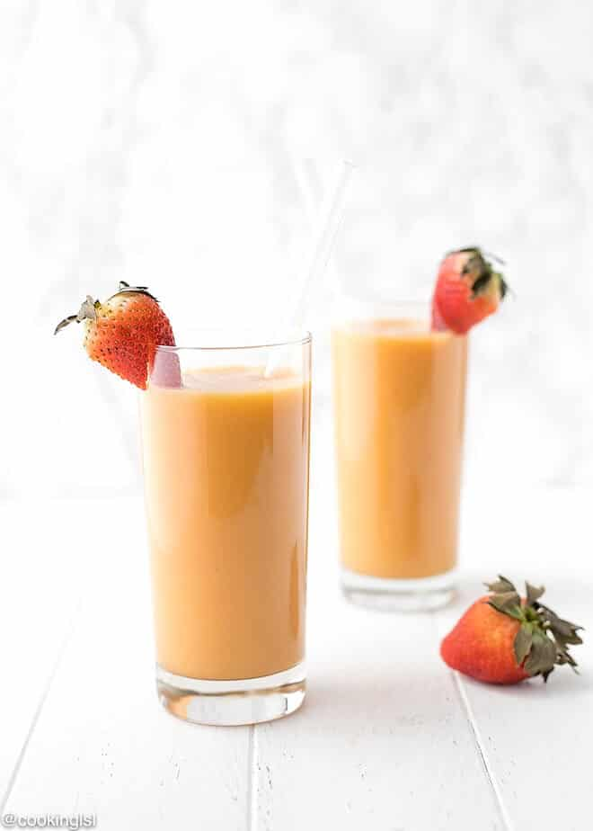 This strawberry mango smoothie i in clear glasses with a straw and strawberries