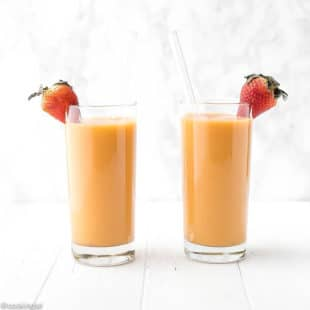 This strawberry mango smoothie i in a tall clear glass with a straw