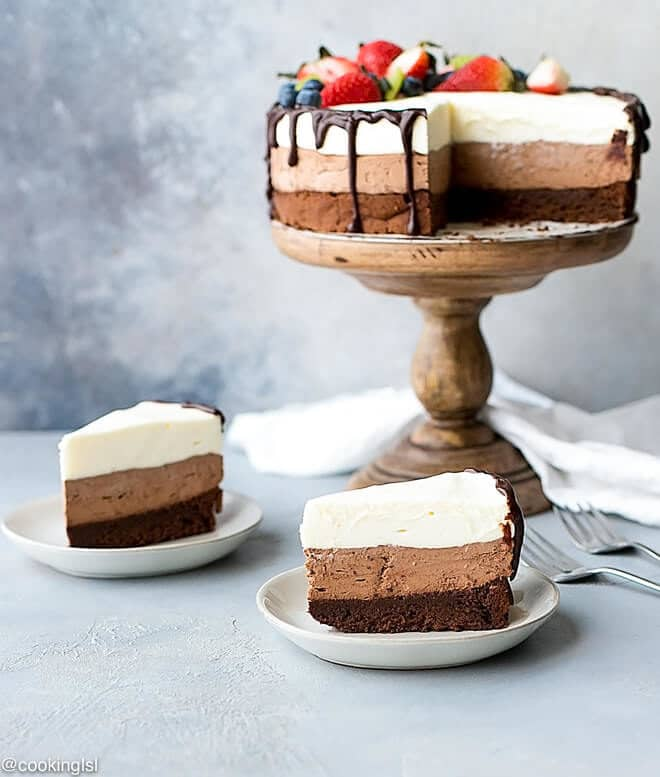 Slices of Triple Chocolate Mousse Cake, with the cake on a stand behind them.