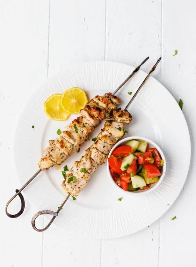 Grilled Chicken Skewers ON A WHITE PLATE WITH SALAD ON THE SIDE