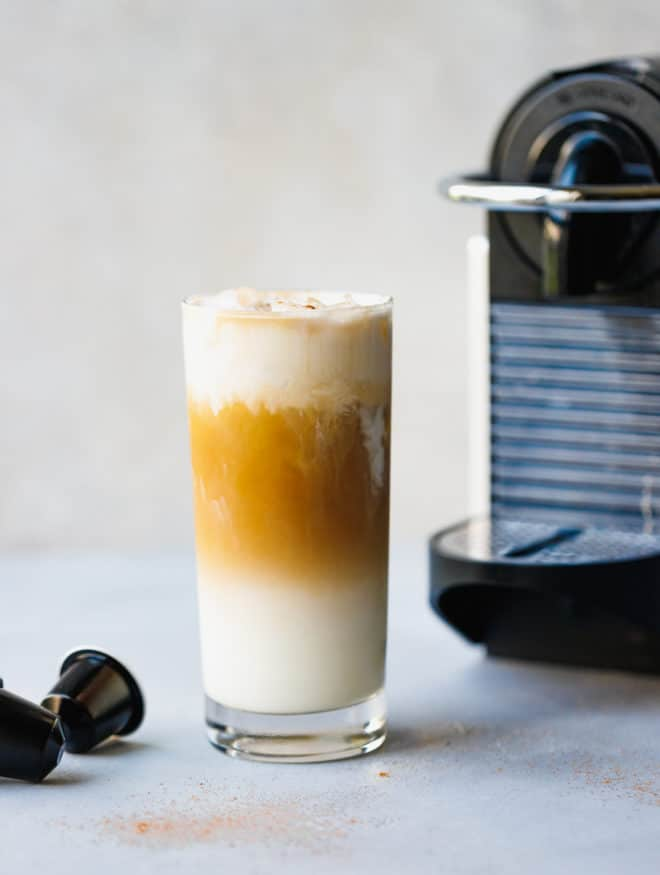 Iced Vanilla Coffee Latte Recipe Using Nespresso in a glass with coffeemaker next to it