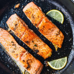 Easy pan seared salmon in a cast iron skillet with lemon slices