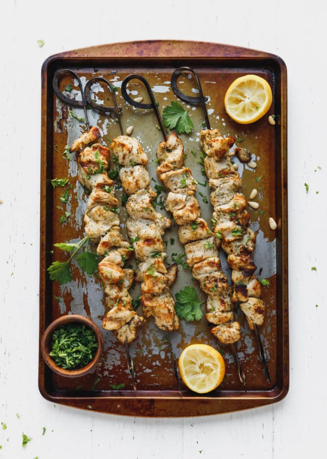 pesto marinated chicken kebabs on a baking sheet