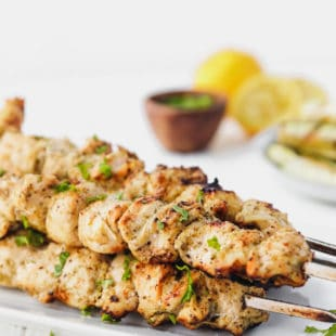 esto marinated chicken kebabs on metal skewers on a plate