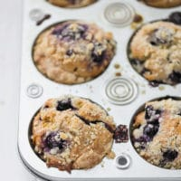 Blueberry Muffins With Olive Oil, Yogurt and Streusel Topping in a muffin tin