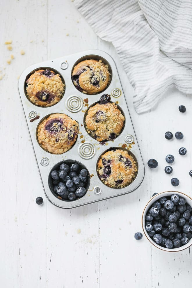 Blueberry Muffins With Olive Oil, Yogurt and Streusel Topping in a silver muffin tin