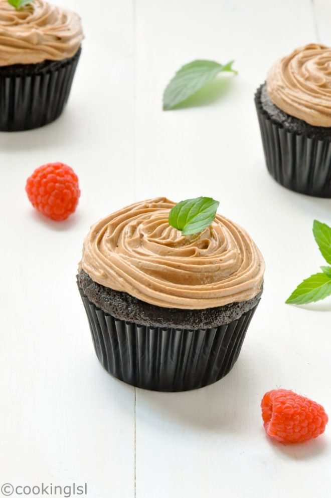 Moist, rich and delicious eggless chocolate cupcakes with creamy Prague frosting. Easy to make, topped with mint and raspberries.
