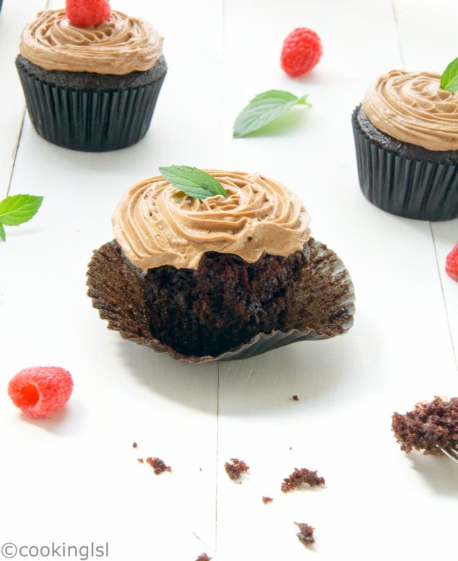 Eggless chocolate cupcakes.Moist, rich and crumby. Fine crumb, made with olive oil. Topped with delicious egg yolk and condensed milk Prague frosting. Topped with mint, placed over white wooden board. Perfect for a party.