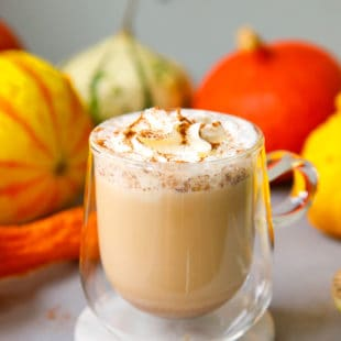 A clear glass with homemade pumpkin spice latte and whipped cream