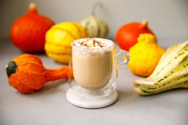 Vegan PSL in a clear glass with pumpkins around it