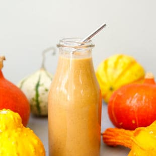 Pumpkin spice smoothie in a glass bottle with a metal straw