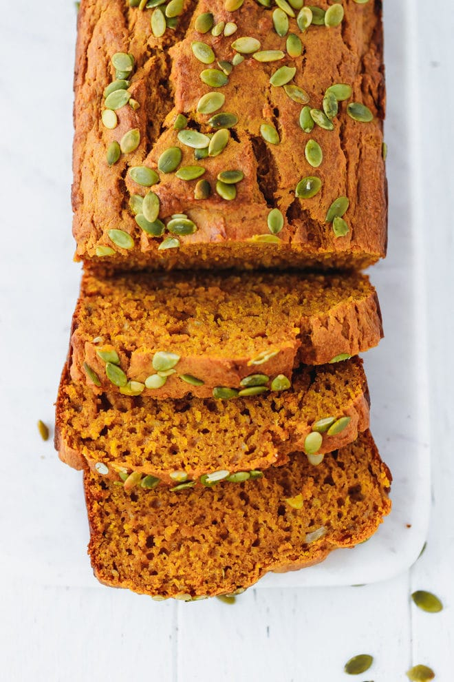 Sliced moist pumpkin bread on a white cutting board