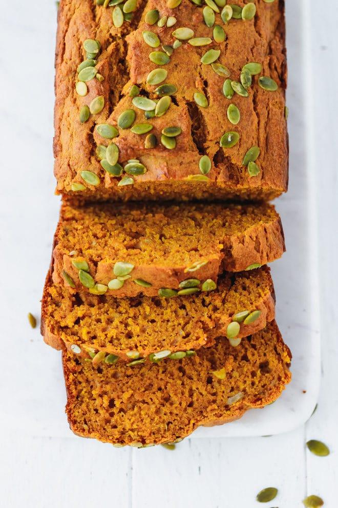 Sliced moist pumpkin bread on a white cutting board