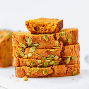 Slices of moist pumpkin bread stacked on top of each other