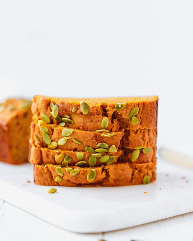 Slices of moist pumpkin bread topped with pumpkin seeds