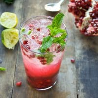 Winter NYE Pomegranate Mojito Cocktail, in a tall clear glass, with pomegranate seeds, lime juice, simple syrup and fresh mint.