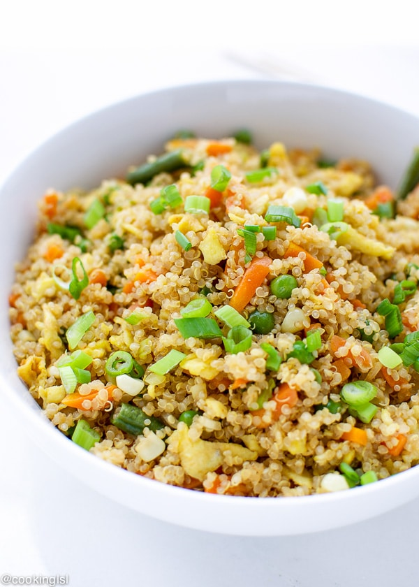 EASY QUINOA FRIED RICE with scrambled eggs in a bowl with soy sauce on the side.