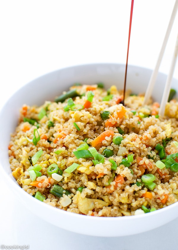 EASY QUINOA FRIED RICE with scrambled eggs in a bowl with soy sauce drizzle