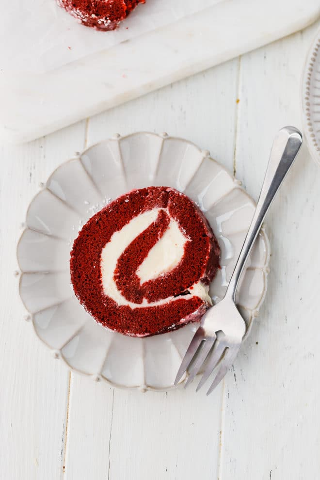 A slice of Red Velvet cake roll on a plate
