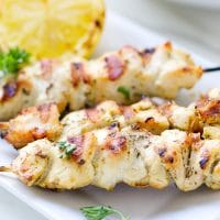 Chicken Skewers With Cabbage Slaw on a white plate, juicy, with lemon wedge