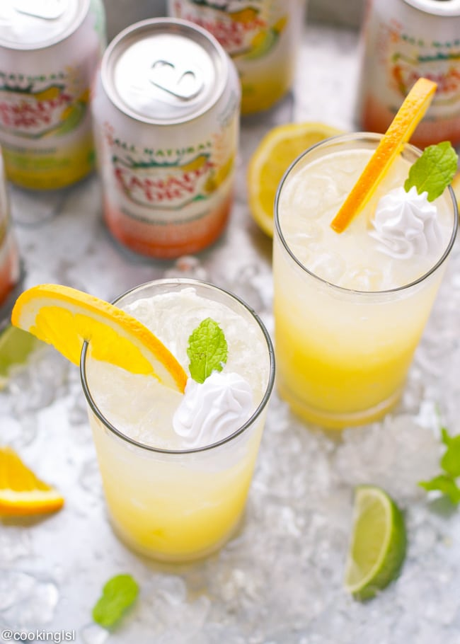 How to make a Refreshing Orange Creamsicle Cocktail, made with vodka, orange juice, sparkling water and topped with whipped cream, orange slice and mint. Summer favorite. Serve with ice.