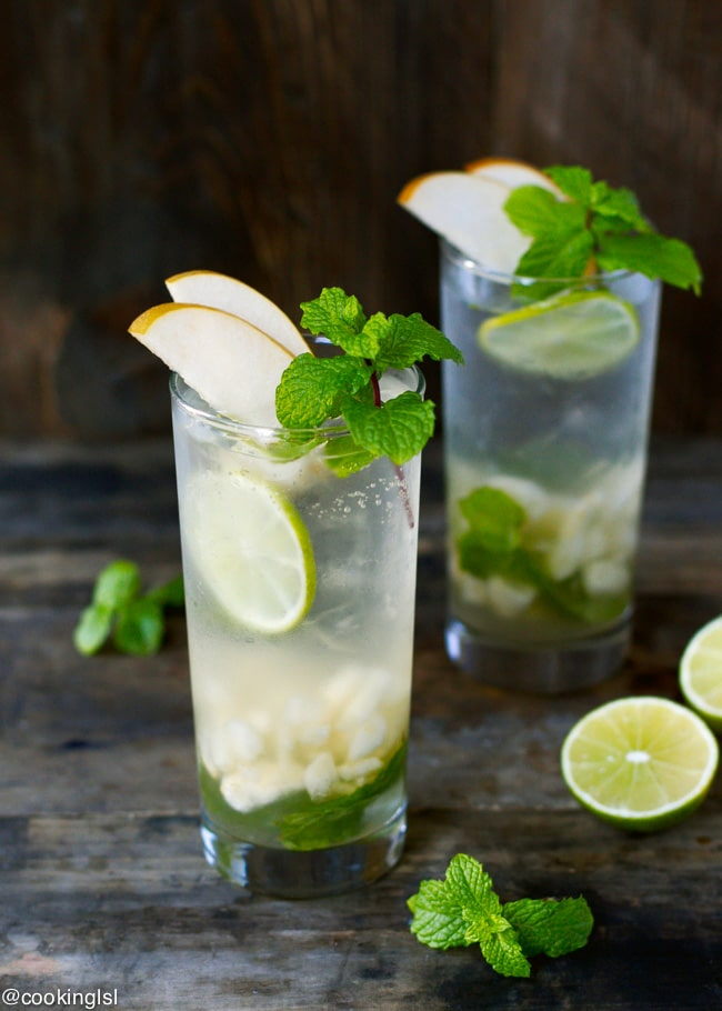 Two tall clear glassed full with delicious, fresh Asian Pear Mojito. Topped with pear slices and fresh mint. Lime on the side.