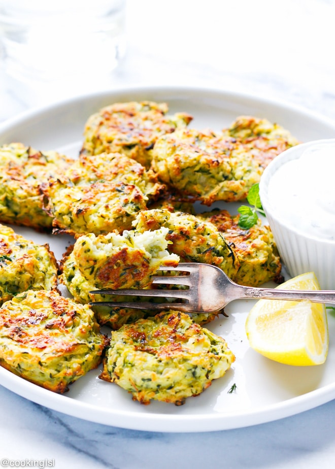 zucchini and feta fritters on a plate with tzatziki