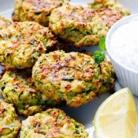 Zucchini and feta fritters on a white plate with lemon wedge