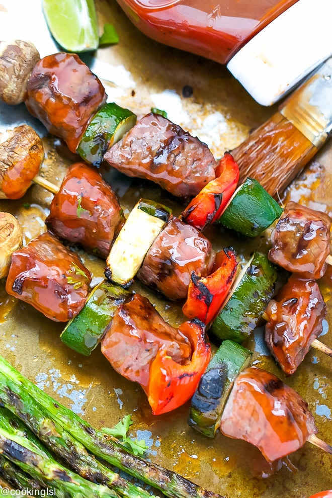 Tender beef kebabs, beef kabobs with tangy Heinz barbecue sauce. Served on a tray with grilled veggies. Skewered on wooden skewers with zucchini, mushrooms and peppers.