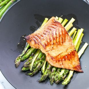 Miso salmon with asparagus on a black plate