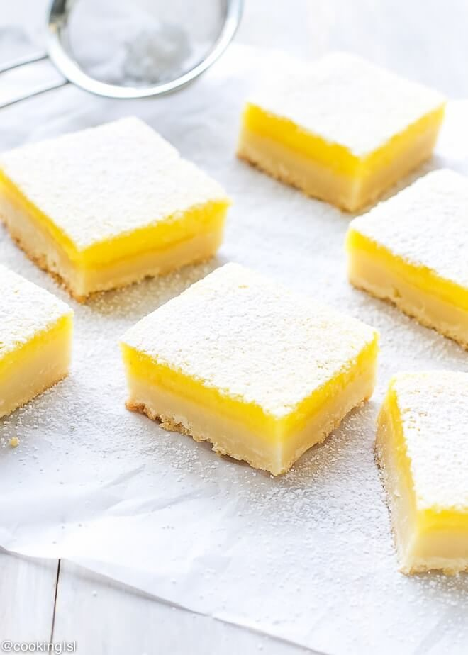 Impressive classic lemon bars with thick, buttery shortbread crust, tangy and fresh lemon curd, baked to perfection and dusted with powder sugar. Great for a party.