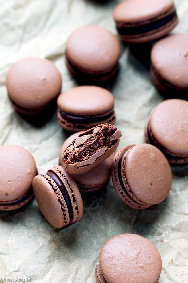 chocolate macarons with ganache and a bite taken into one of them