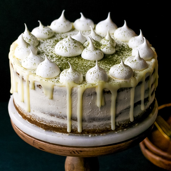 matcha layer cake, thin layers, made from scratch, with whipped mascarpone cream filling, naked, white chocolate ganache drip and meringue cookies