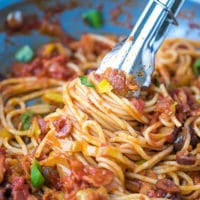 A pan with spaghetti with tomato pepperoncini peppers sauce and bacon. Thongs with spaghetti