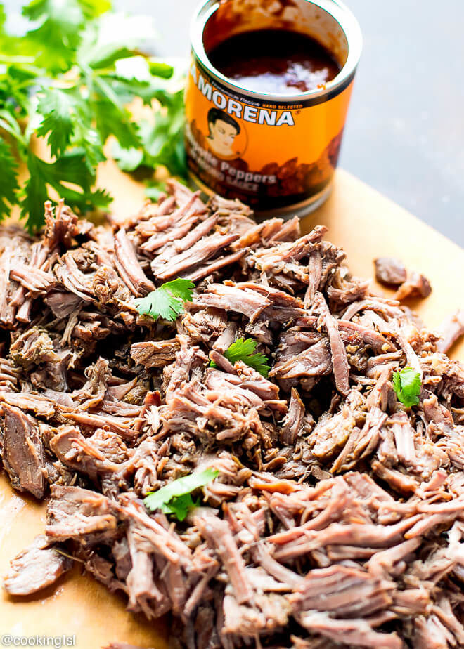 Shredded easy barbaoa recipe - slow cooker, meat on a cutting board chipotle peppers in adobo.
