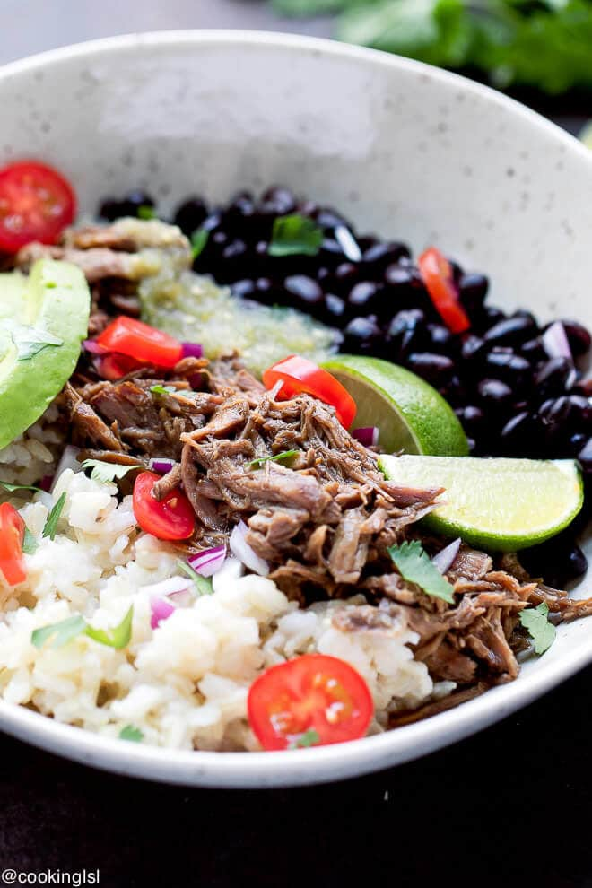 A rice bowl made with Slow Cooker Easy Barbacoa recipe with black beans brown rice lime salsa avocado tomatoes.