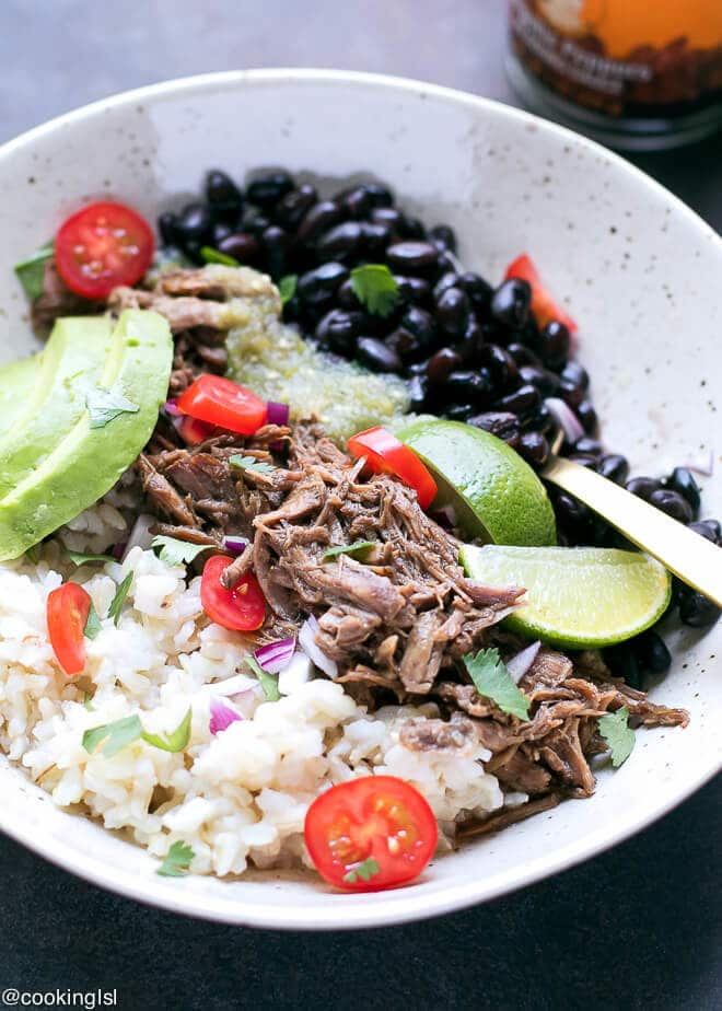 Rice bowl Chipotle Style made with this Easy Barbacoa Recipe. Tender Barbacoa Beef Chunk Roast in a bowl with rice, beans, avocado, lime, salsa and tomatoes.