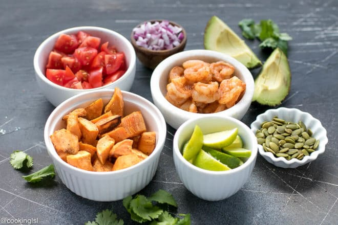 Ingredients needed for shrimp rice bowl. Chopped tomatoes, shrimp, avocado, cilantro, roasted sweet potatoes, lime, pepitas and red onion.