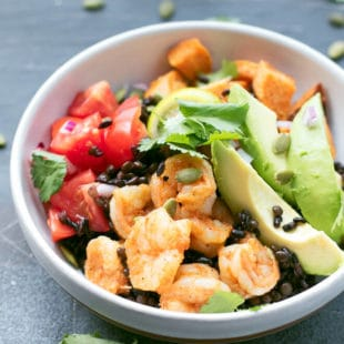 Grain bowl with black rice, black qionoa, black lentils, sliced avocado, shrimp, roasted sweet potoato cubes, tomatoes and topped with cilantro and pumpkin seeds.