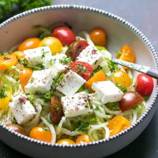 A bowl full with spiralized cucumber, chopped cherry tomatoes, onion, parsley, olive oil, salt, apple cider vinegar and cubed feta cheese, sprinkled with sumac.