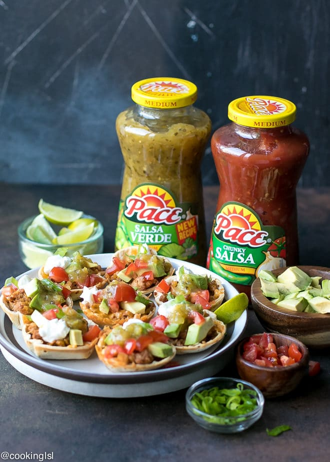 Crunchy Taco Cups With Tortillas, turkey and salsa verde recipe. Made with Pace® Salsa and perfect for a game day appetizer. A plate with mini taco appetizer, topped with avocado, sour cream and tomatoes.