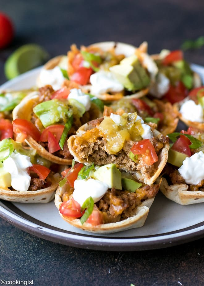 Crunchy Taco Cups With Tortillas, turkey and salsa verde recipe. Made with Pace® Salsa and perfect for a game day appetizer. A plate with mini taco appetizer, topped with avocado, sour cream and tomatoes. A bite into a mini taco cup.