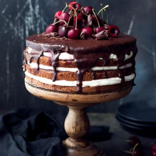 A wooden cake stand with gorgeous cherry, whipped cream, chocolate cake. Easy black forrest cake recipe, perfect for a summer celebration.