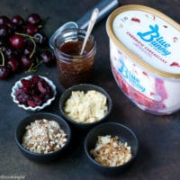 Bowls with ice cream mix ins, to make Cherry Sundae Recipe. A container of Blue Bunny® Ice Cream. Homemade chocolate sauce, fresh cherries, almonds, coconut flakes and lady finger crumbs.