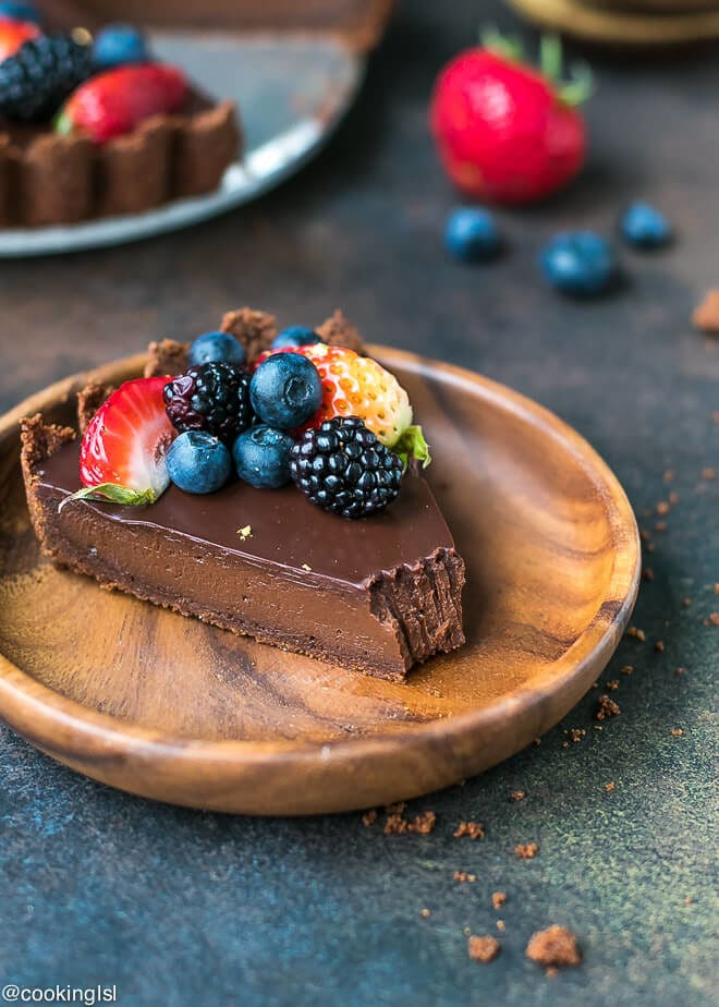 A wooden bamboo plate with a slice of decadent and delicious dark chocolate tart, topped with fresh berries.