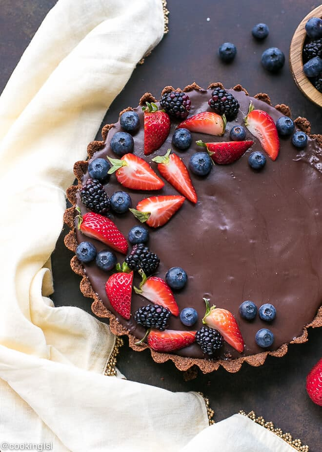 Dark Chocolate Tart Rart. Simple homemade tart with graham cracker crust, topped with fresh berries. With a blow of berries on the side. Perfect for a party year round.